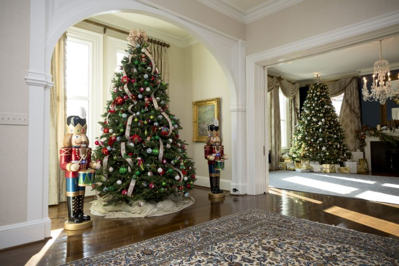 In the foyer, a Christmas tree stands in the nook, decorated with ornaments created by participants in the Art Therapy Program at Riley Hospital for Children at IU Health in Indianapolis, Indiana. A nutcracker stands on each side of the tree.