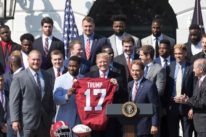 President Donald J. Trump receives an Alabama team jersey during ceremonies celebrating the 2017 College Football National Champions the Alabama Crimson Tide, on the South Lawn at the White House, Tuesday, April 10, 2018, in Washington, D.C.