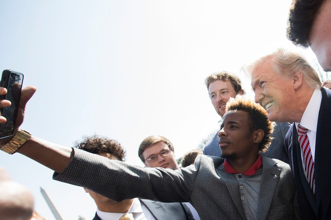 President Donald J. Trump poses for selfies with members of the Alabama football team, during ceremonies celebrating the 2017 College Football National Champions the Alabama Crimson Tide, on the South Lawn at the White House, Tuesday, April 10, 2018, in Washington, D.C.