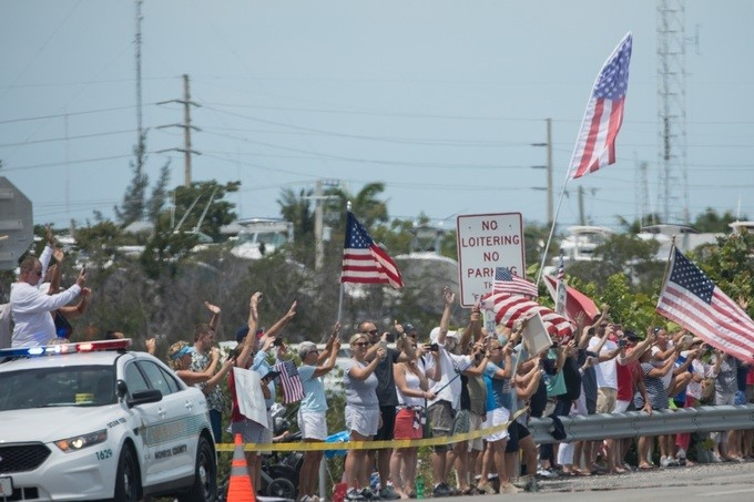 Supporters and service members line the streets to wave to President Donald J. Trump's motorcade, Thursday, April 19, 2018, in Key West, Florida.
