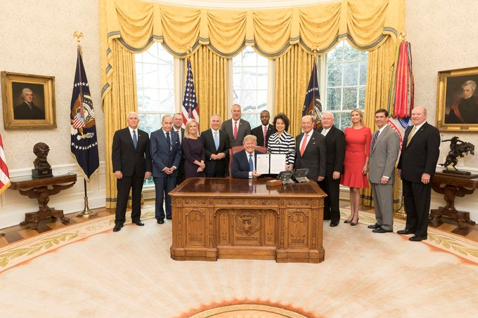 """President Donald J. Trump, joined by Vice President Mike Pence and members of his Cabinet, from left to right, Director of the National Economic Council Larry Kudlow; Director of the Office of Management and Budget Mick Mulvaney; Secretary of Homeland Security Kirstjen Nielsen; Administrator of the Environmental Protection Agency Scott Pruitt; Secretary of Interior Ryan Zinke; Secretary of Housing and Urban Development Ben Carson; Secretary of Transportation Elaine Chao; Secretary of Commerce Wilbur Ross; Secretary of Agriculture Sonny Perdue; Assistant to the President Ivanka Trump; Secretary of the Army Mark T. Esper, and Assistant Secretary of the Army Ricky """"R.D."""" James, holds the signed One Federal Decision Memorandum of Understanding in the Oval Office at the White House, Monday, April 9, 2018, in Washington, D.C., which establishes a coordinated and timely process for environmental reviews of major infrastructure projects."""